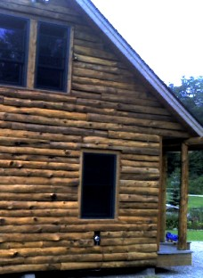 hand peeled natural log siding installed on log cabin by greenleaf forestry