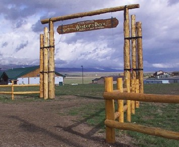 Tall log entry way with sign western days built by greenleaf forestry craftsmen